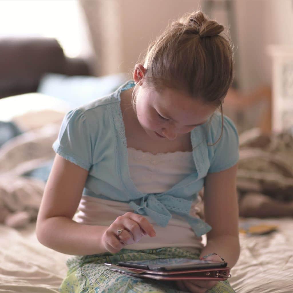 Meisje op bed met tablet en de gevolgen van bijziendheid bij kinderen